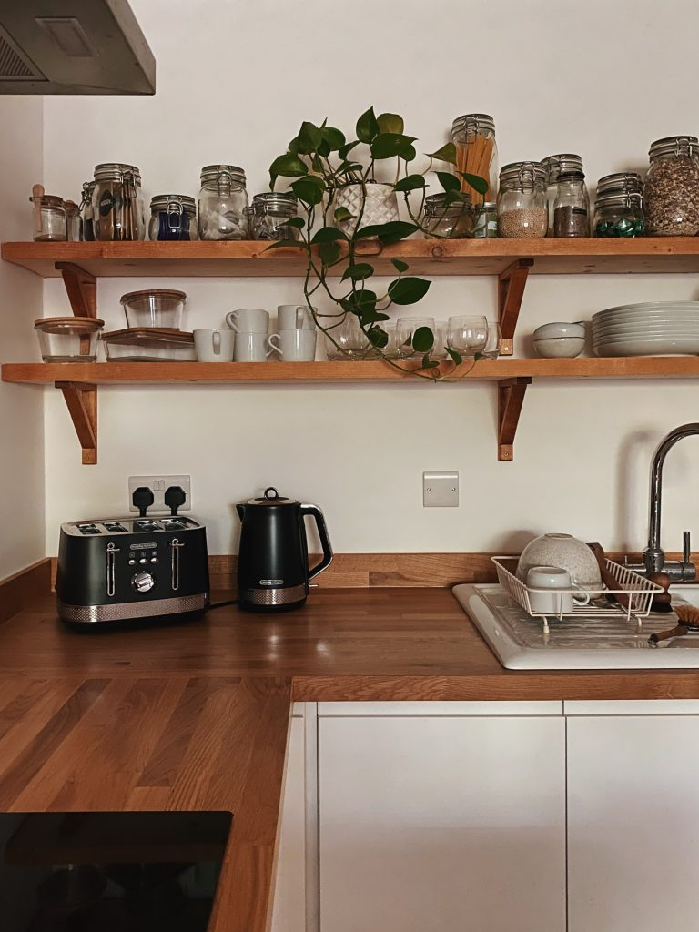 a white kitchen with white units.  A set of shelves above the worktop holds plants in pots and glass jars with pasta and grains in it and lots of crockery. A toaster and kettle sit on the worktop and there's are plates and bowls on the drainer.