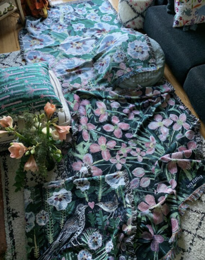 a variety of floral blankets and cushions on a wooden floor in blacks, blues, lilacs and greens