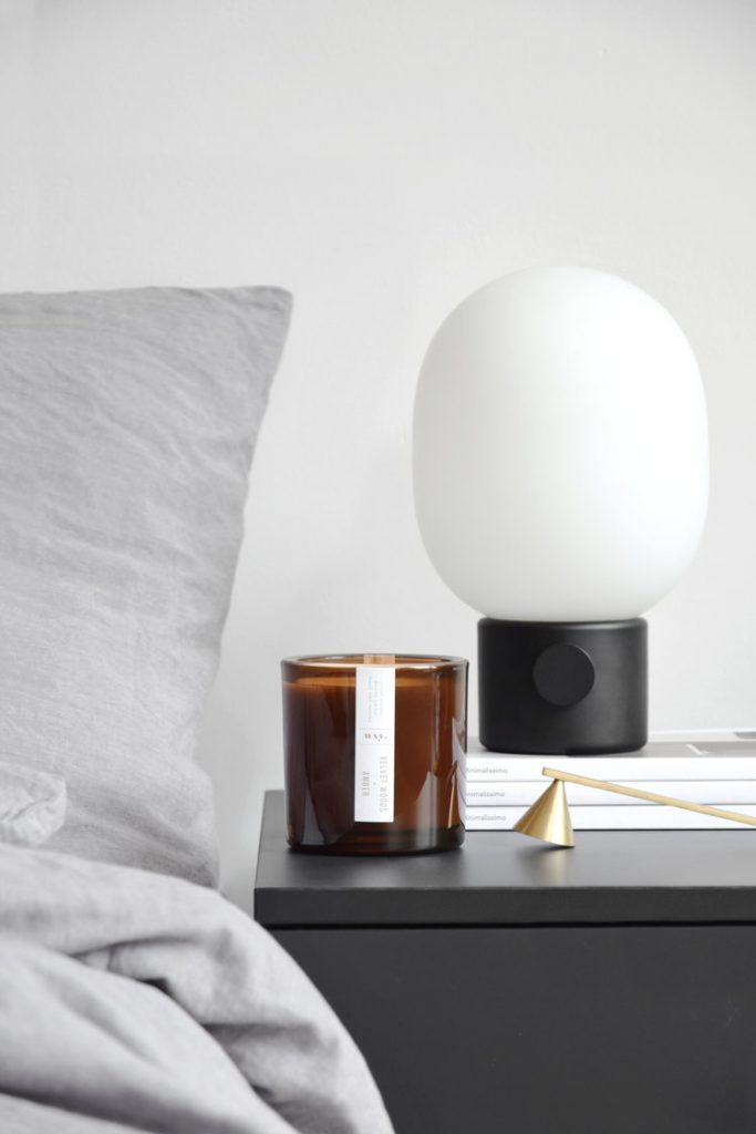 Image of a candle in a smoked glass holder, on a bedside table, next to a black and white lamp