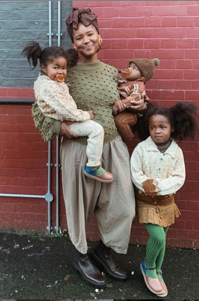 A young woman is smiling to the camera while holding two of her children while her older daughter stands at her side. They stand in front of a red brick wall and wear a tonal palette of cream, taupe, khaki, sand and rust.