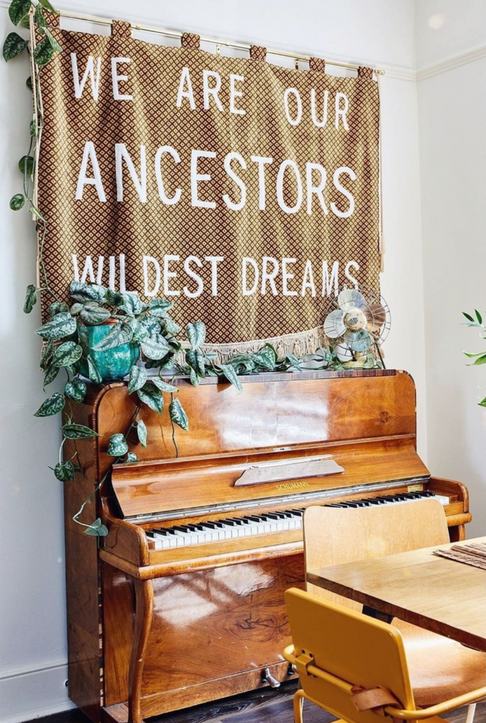 a banner reading 'you are your ancestors wildest dreams' in brown is hung above a highly polished piano with a plant on top
