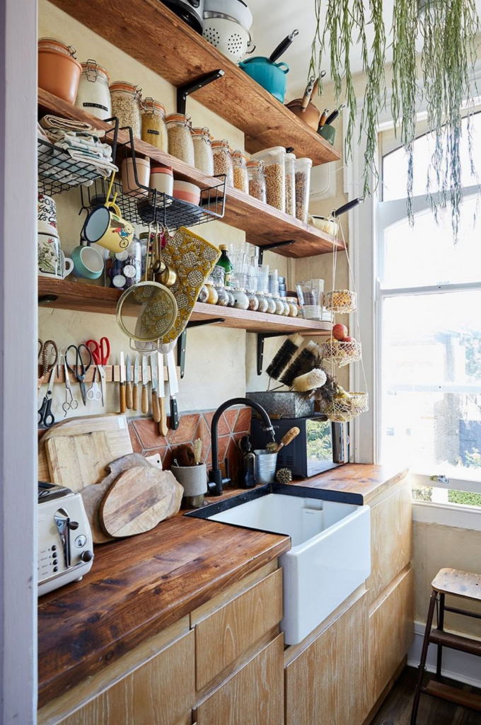a wooden kitchen with a butler sink with chopping boards and a toaster on. Above are magnetic knife and scissor blocks with terracotta tiles behind. There are shelves above with many kilner jars with food in with pans above them.