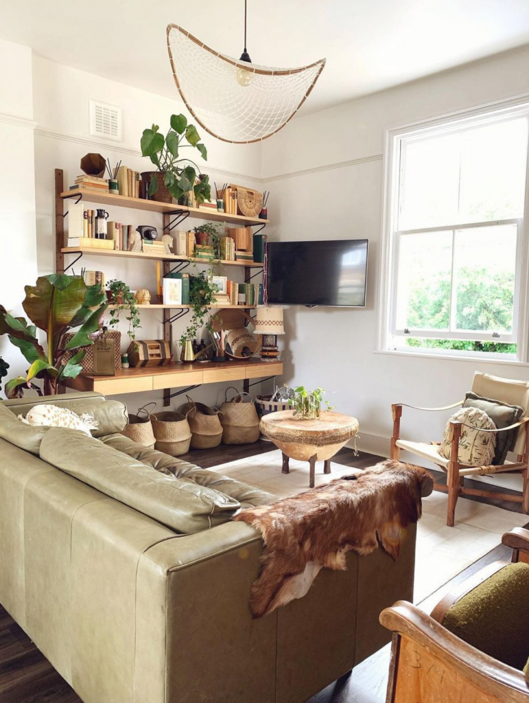 a set of wooden shelves hold many books and ornaments of complimentary colours. under it is a row of baskets. There is a wicker coffee table and a armchair with beige and green cushions sits next to it. In front of it is a green leather sofa with cow cowhide rug on the arm,