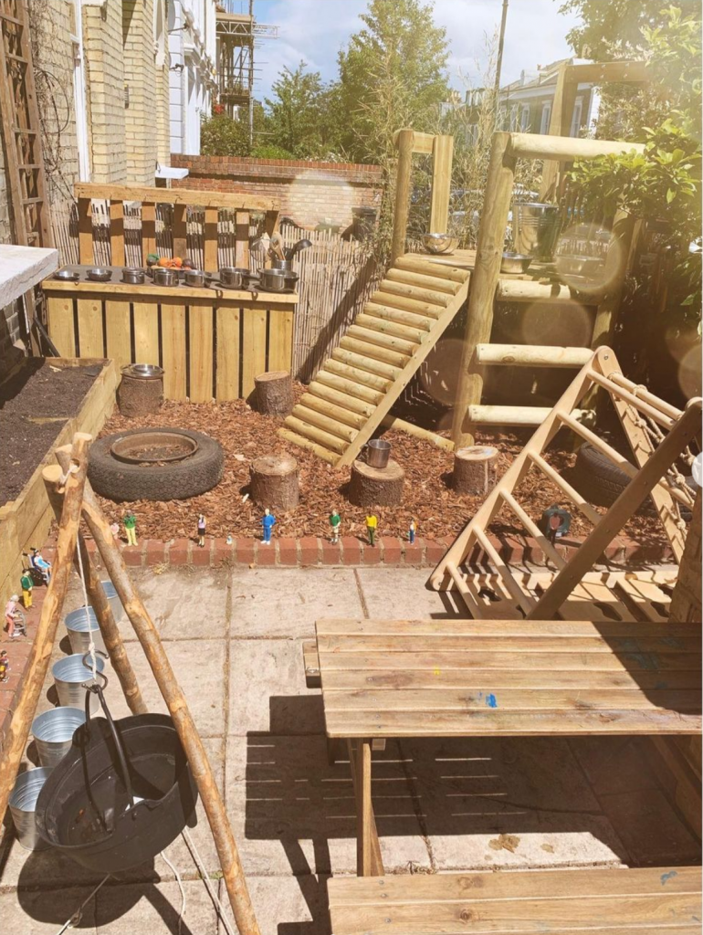 a wooden play area with a climbing platform, ladder, woodchippings and raised beds sits in the front garden of a suburban street