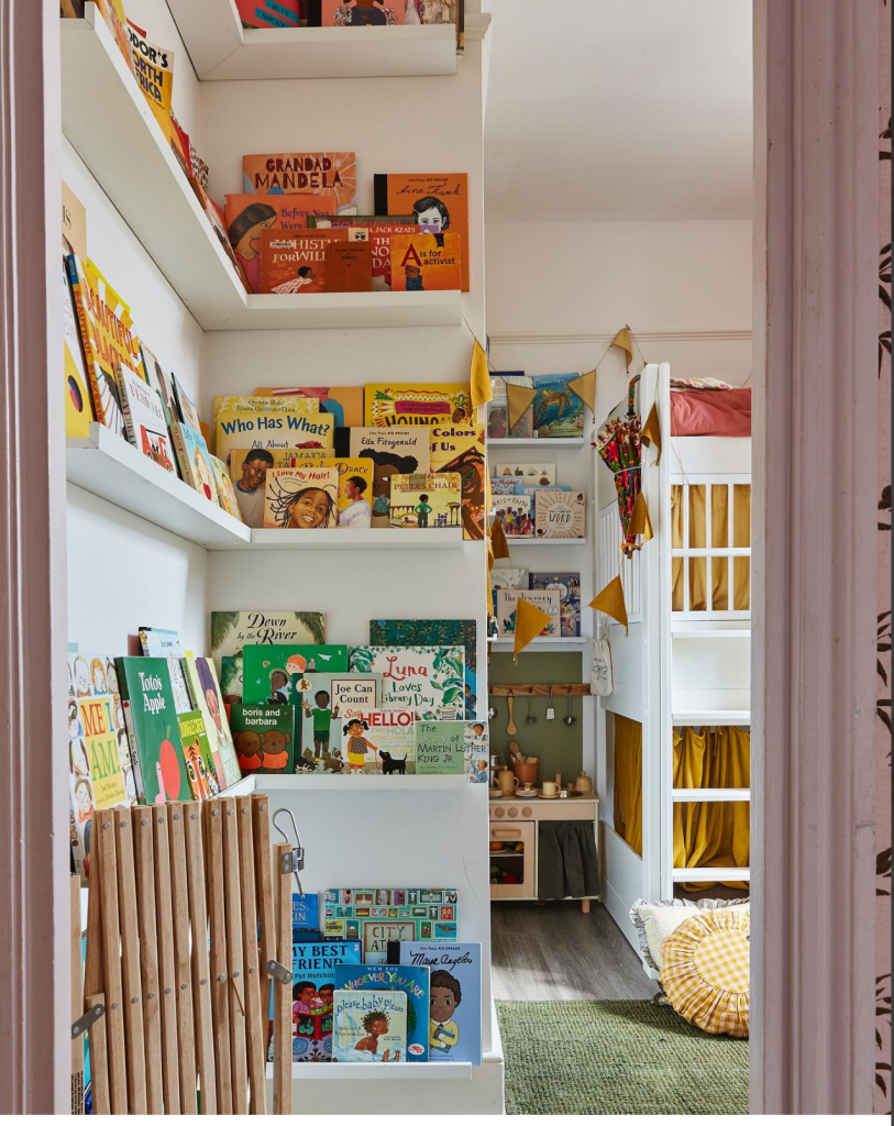 A room has many picture shelves with books on arranged according by colour from blue on the bottom to green and then yellow and then orange. There is a white wall behind. to the right is a children's wooden toy kitchen with more books above and to the right of that is a white bunk bed with yellow curtains and there is a green rug in front with a yellow round cushion sat on it