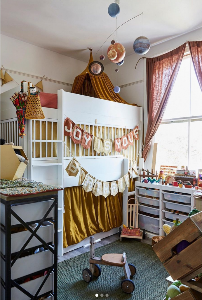 A white room with a triple decker bunk bed with a curtains in browns and creams and a banner that reads 'joy is your birthright'. A mobile of the solar system hangs above and to the side, below a window are drawers of toy storage