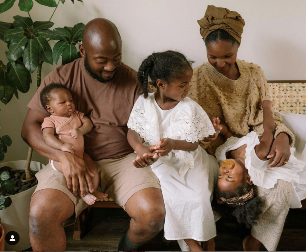 A smiling woman sits on a sofa with her daughter on her lap who is  laughing up at her. Next to her, her older daughter stands wearing a white dress and looking at her sibling. Her father sits next to her holding a small baby in his knee. This young family are all dressed in a tonal palette of white, taupe, camel, brown and pink