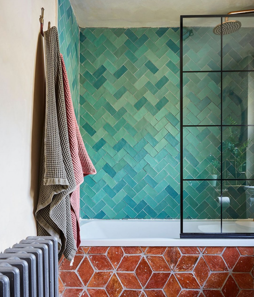 a bath has turquoise tiles in a crosshatch pattern above it and has star patterned terracotta tiles on its front. There is a grey radiator to the left with a pink and taupe towel hung above.