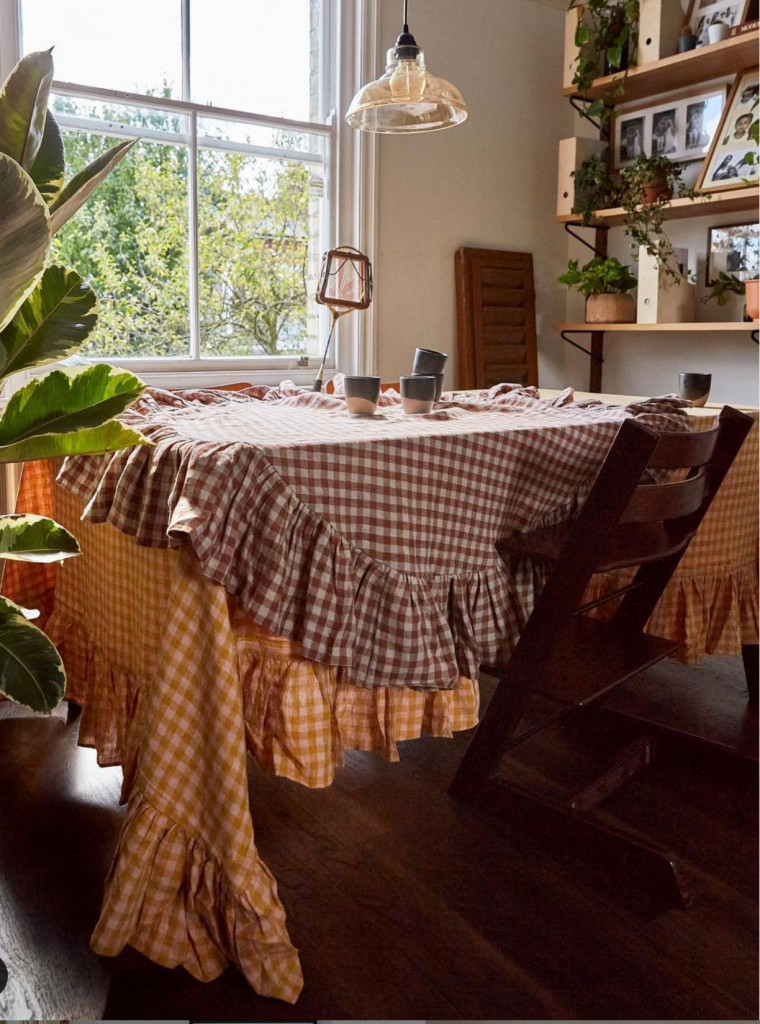 a dining table has orange and red ruffled table cloths on it. A wooden chair is tucked under the table and a tennis racquet sits on the window ledge in front of it. There are wooden shelves to the right filled with plants and photos.