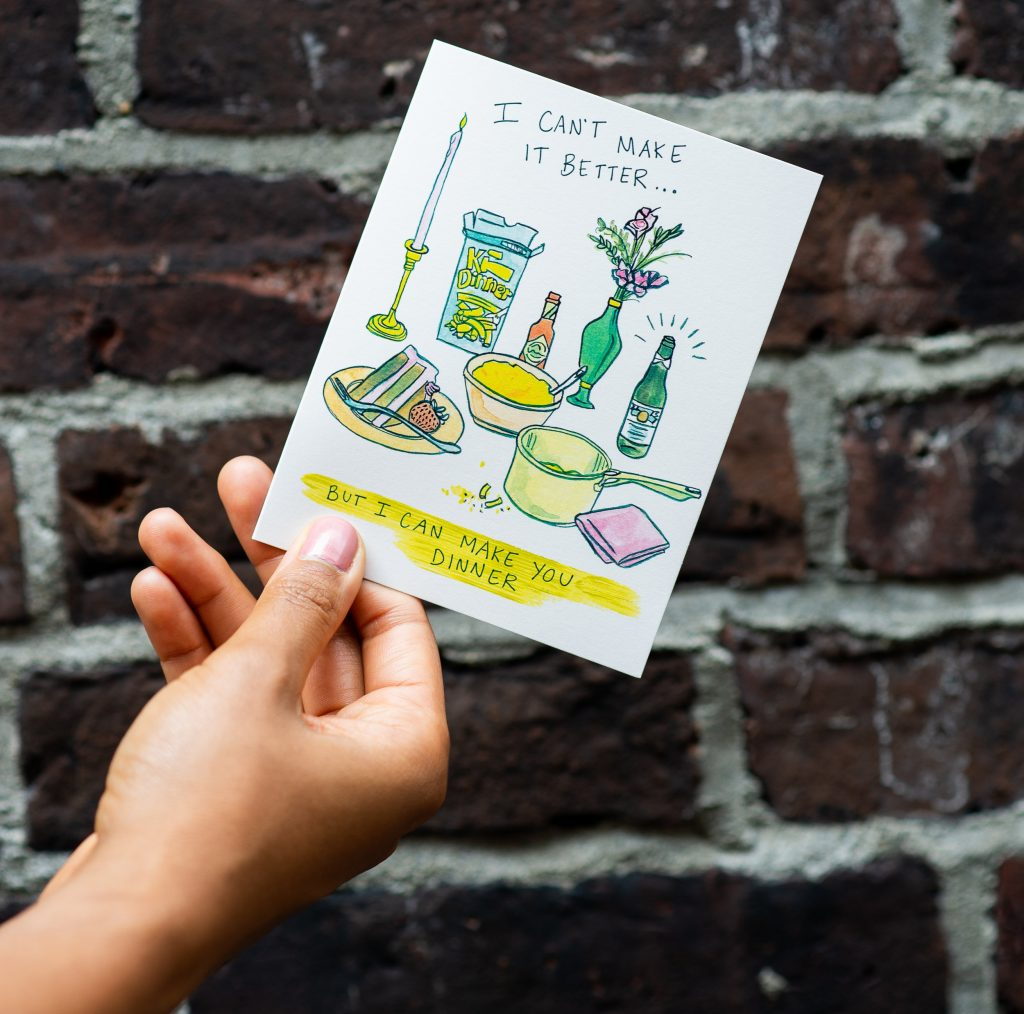 A woman's hand holds a card with illustrated dinner things on it and writing that says, 'I can't make it better... but I can make you dinner'