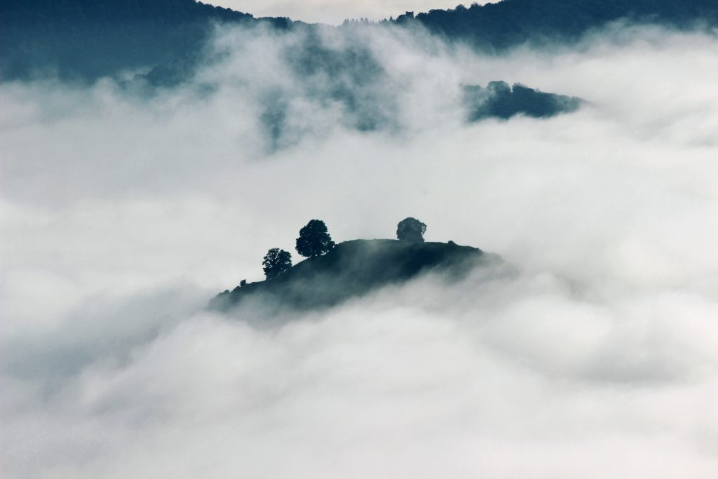 A lone tip of a mountain glimpsed through clouds